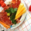 Sliced meat with sauce on board with vegetables — Stock Photo #12096035
