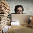 Accountant in problems. Alone working on laptop with a lot of books around on messy table. — Stock Photo #12096450