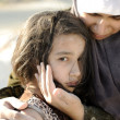 Poverty and poorness on the children face. Sad little girl. Refugee. In Muslim mother's arms. — Stock Photo