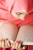 Adorable beautiful girl reading Koran — Stock Photo