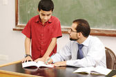 Male teacher in classroom helping a pupil in front of the board — Stock Photo