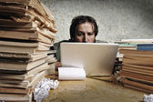 Accountant in problems. Alone working on laptop with a lot of books around on messy table. — Stock Photo