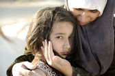 Poverty and poorness on the children face. Sad little girl. Refugee. In Muslim mother's arms. — Photo