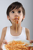 Kid eating spaghetti — Stock Photo