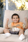 Happy child sitting on sofa — Stock Photo