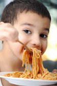 Tasty food, messy child eating spaghetti — Stock Photo