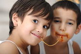 Two little boys eating spaghetti — Stock Photo