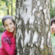 Two little arabic girls playing on the park tree outdoor — Stock Photo #12234643