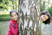 Two little arabic girls playing on the park tree outdoor — Stock Photo