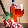 Stock Photo: Wineglass, bottles of wine and grapes