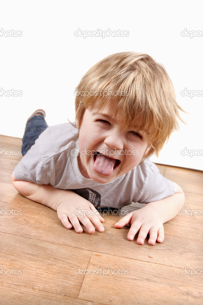 Boy pulling a funny face playing on the floor — Stock Photo #12337914