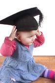 Baby girl wearing university graduation mortar board cap — Stock Photo