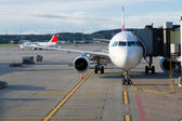 Airplane at an airport with passenger gangway — Stock Photo