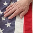 Man with hand on USA flag — Stock Photo