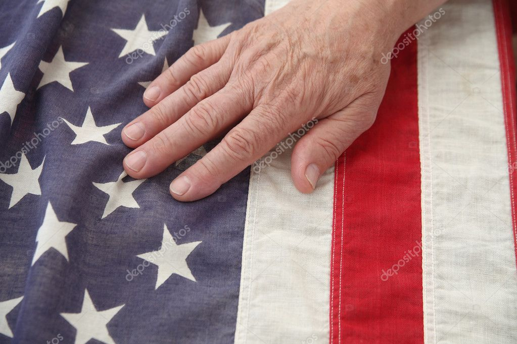 A man's hand on a very old American flag — Stock Photo #10927507