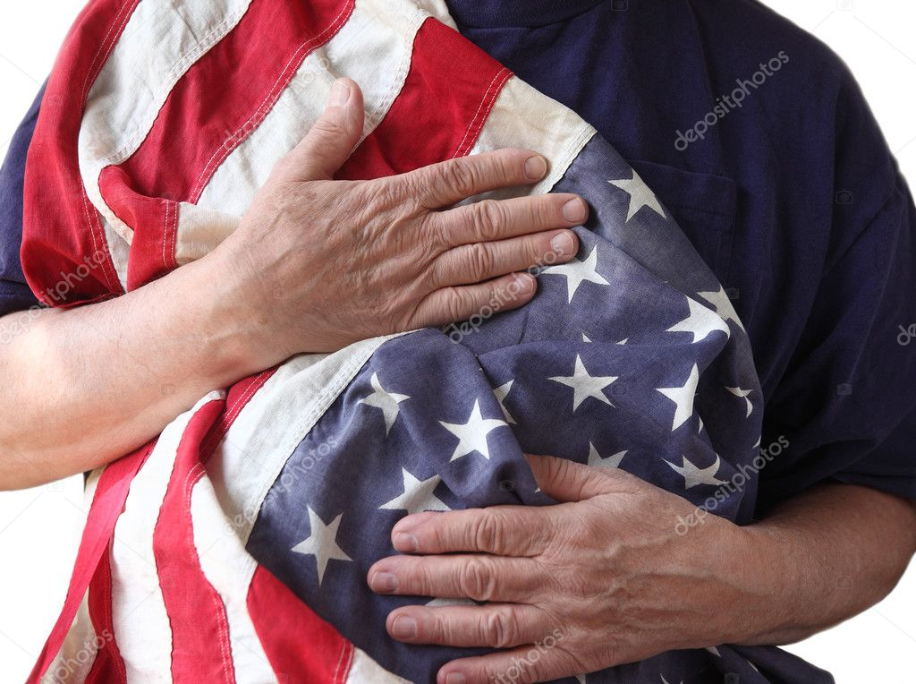 A man holds the American flag close to his body  Foto de Stock   #10927543