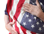Man holds American flag close to his body — Stock Photo