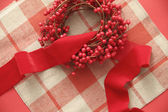 Christmas berries and ribbon on plaid — Stock Photo