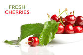 Fresh cherry berries with green leaves isolated on white — Stock Photo