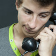 A young man with an old phone — Stock Photo