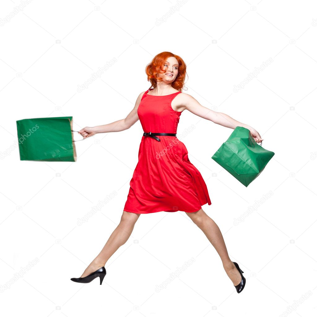 Young adult readhead jumping holding green shopping bags in her hands, isolated on white, studio shot — Stock Photo #11376080