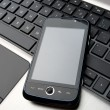 Stock Photo: Modern phone with touchscreen on laptop keyboard