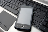 Modern phone with touchscreen on laptop keyboard — Stock Photo