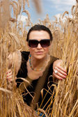 Cute young female sitting in a wheat field — Stock Photo