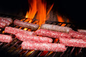 Brats cooking on the grill — Stock Photo