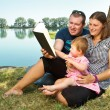 Boy and girl with books on the nature near lake — Stock Photo