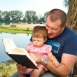 Stock Photo: Father and little girl reading book