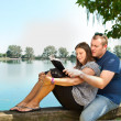 Boy and girl with books on the nature near lake — Stock Photo #11579273