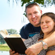 Boy and girl with books on the nature near lake — Stockfoto #11579427