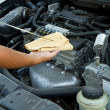 Auto mechanic checking oil - Stock Photo