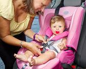 Femme, son fils de fixation sur un siège de bébé — Photo