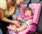 Woman fastening her son on a baby seat — Stockfoto