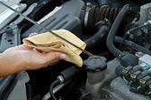 Auto mechanic checking oil — Stock Photo