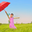 Teenage girl with red umbrella in wheat field — Stock Photo