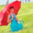 Teenage girl with red umbrella in wheat field — Stock Photo #10963597