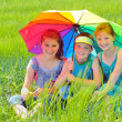 Kids with umbrella on field — Stock Photo