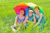 Kids with umbrella on field — Stock Photo