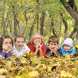 Kids lying on leaves — Stock Photo