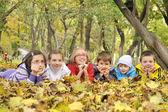 Kids lying on leaves — Stock Photo