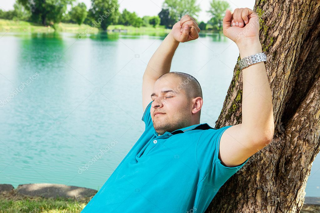 Man is stretching while leaning on a tree and relaxing  Stock Photo #11566588