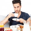 Man is having breakfast in the bed — Stock Photo