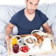 Man is having breakfast in the bed — Stock Photo #11929478
