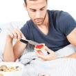 Man is having breakfast in the bed — Stock Photo #11929542