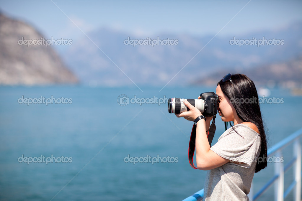 Sexy brunette is holding a dslr and taking a picture — Stock Photo #12274376