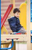 Boy sits on playground — Stock Photo
