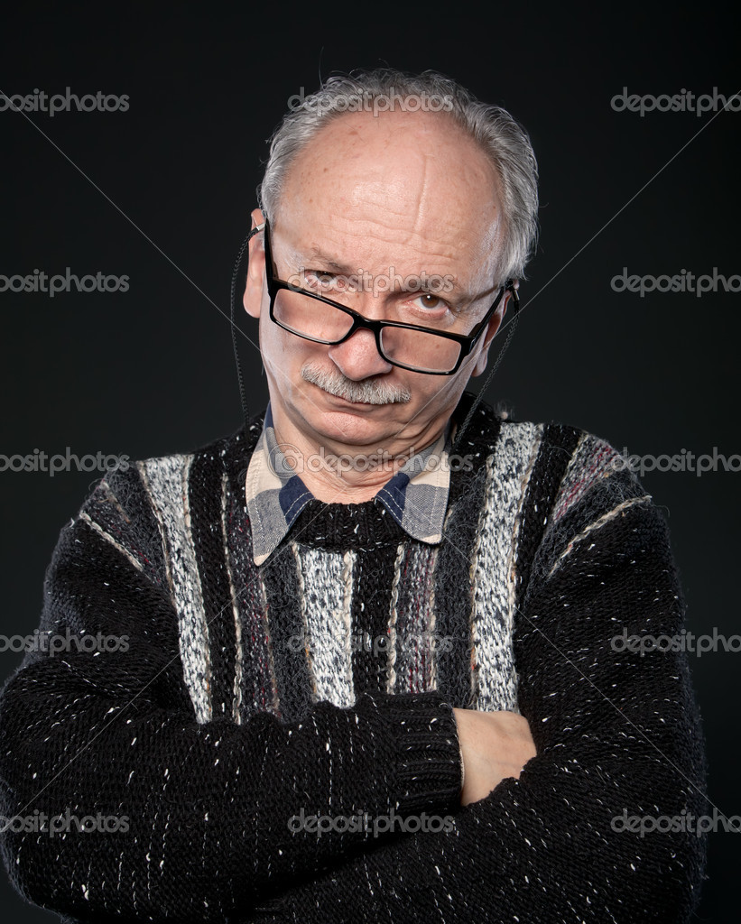 An elderly man with glasses and crossed arms looks skeptically on a dark background — Stock Photo #10891669
